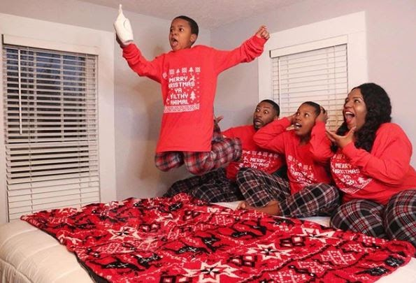 family with kids jumping on bed