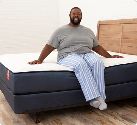 plus size man sitting on bed